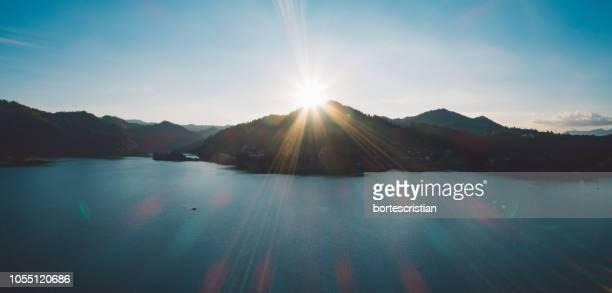 scenic view of lake and mountains against bright sun - bortes fotografías e imágenes de stock