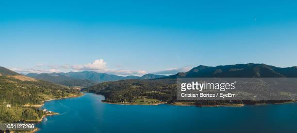 scenic view of lake and mountains against clear blue sky - bortes fotografías e imágenes de stock