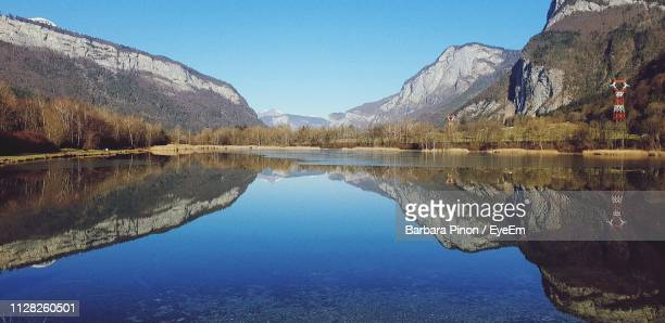 scenic view of lake and mountains against clear blue sky - sallanches stock pictures, royalty-free photos & images