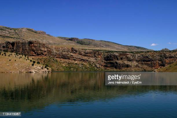 scenic view of lake and mountains against clear blue sky - jens helmstedt stock-fotos und bilder