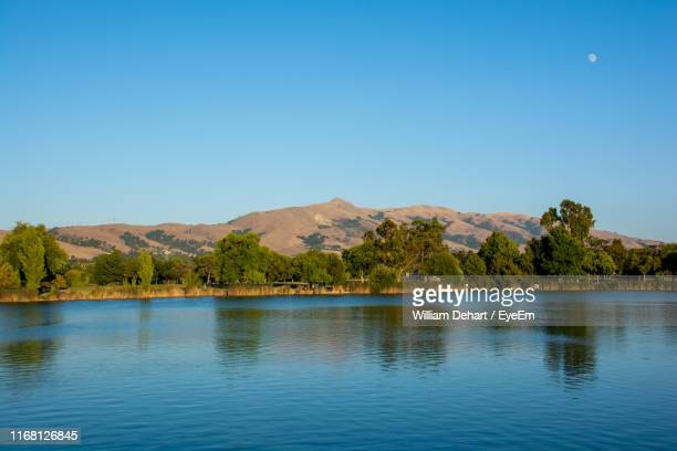 scenic view of lake and mountains against clear blue sky - william moon stock pictures, royalty-free photos & images