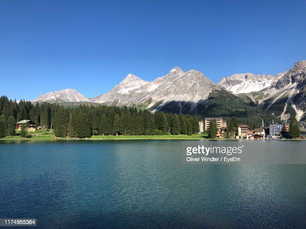 scenic view of lake and mountains against clear blue sky - アロサ ストックフォトと画像