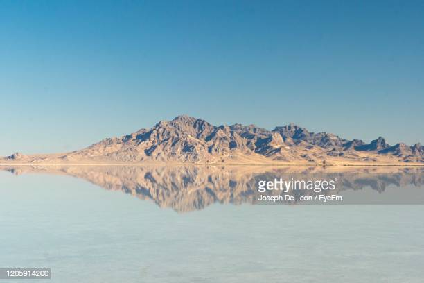 scenic view of lake and mountains against clear blue sky - bonneville salt flats stock pictures, royalty-free photos & images