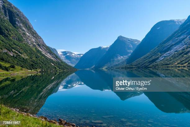 scenic view of lake and mountains against clear blue sky - noruega fotografías e imágenes de stock