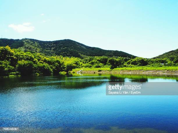 scenic view of lake and mountains against clear blue sky - 池 ストックフォトと画像