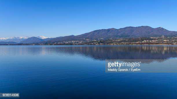 scenic view of lake and mountains against clear blue sky - varese stock pictures, royalty-free photos & images