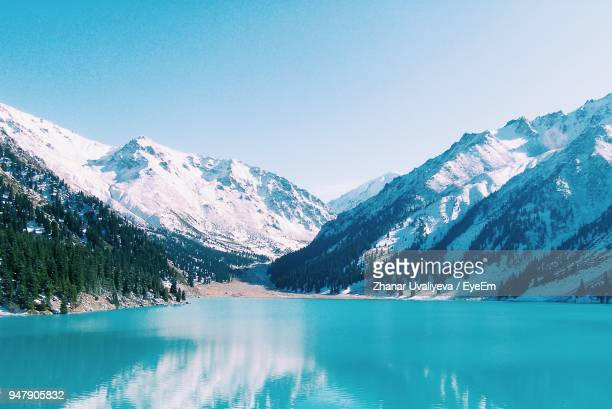 scenic view of lake and mountains against clear blue sky - kazakhstan stock pictures, royalty-free photos & images