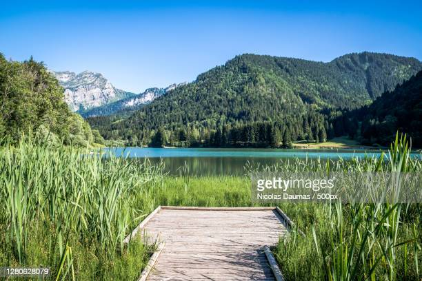 scenic view of lake and mountains against clear blue sky,chemin du col,france - travel photos et images de collection