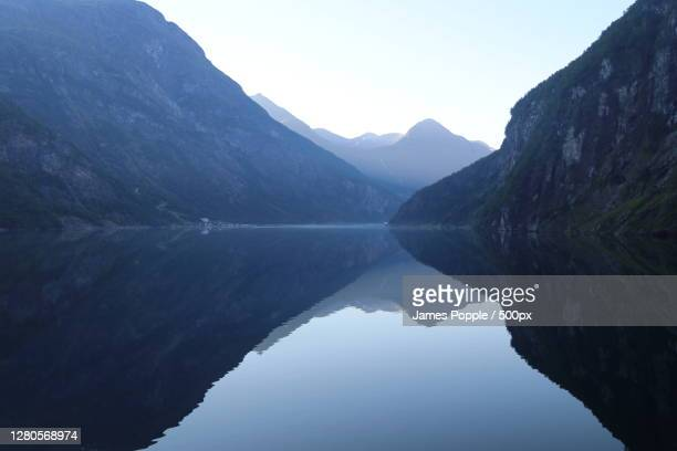 scenic view of lake and mountains against clear sky, geiranger, norway - james popple foto e immagini stock