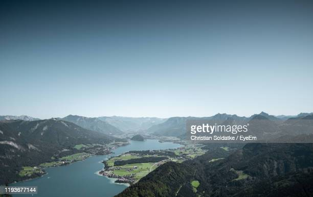 scenic view of lake and mountains against clear sky - christian soldatke stock pictures, royalty-free photos & images