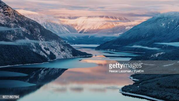 Scenic View Of Lake And Mountains Against Cloudy Sky During Winter