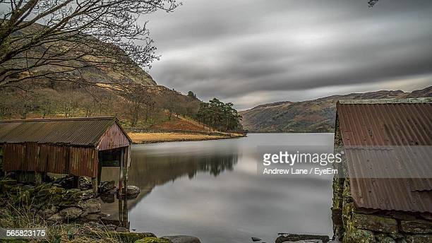 scenic view of lake and mountains against cloudy sky - gwynedd stock photos and pictures