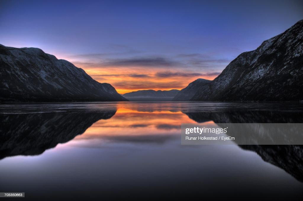 Scenic View Of Lake And Mountains Against Dramatic Sky : Stock Photo