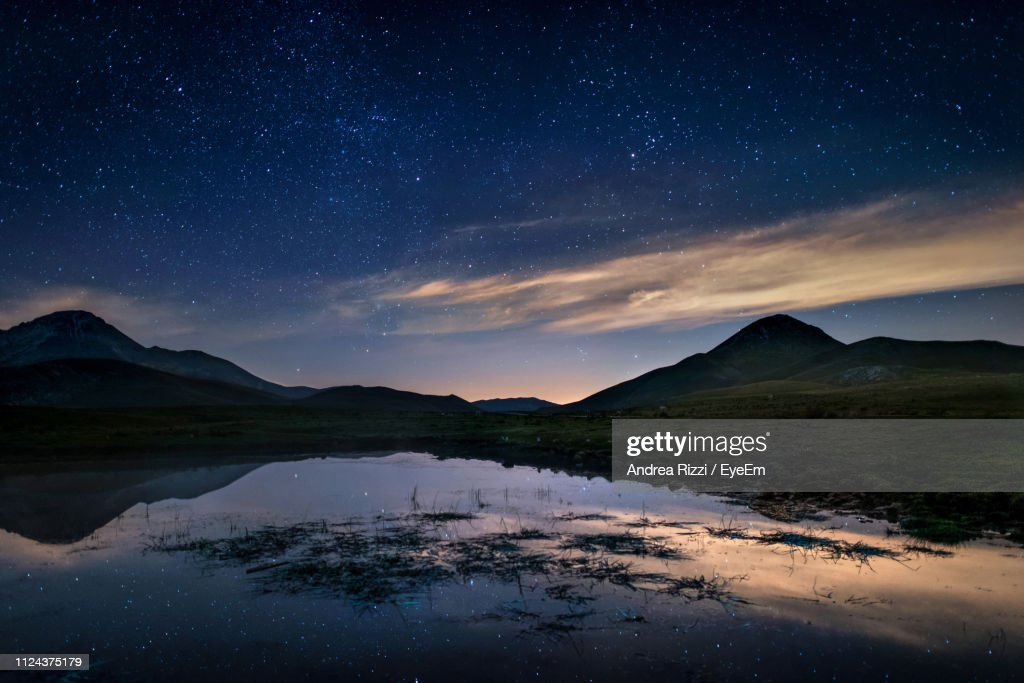 Scenic View Of Lake And Mountains Against Sky At Night : Foto de stock