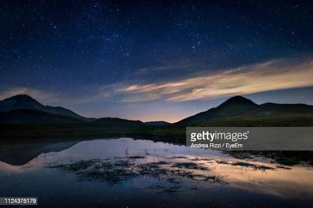 scenic view of lake and mountains against sky at night - andrea rizzi stockfoto's en -beelden