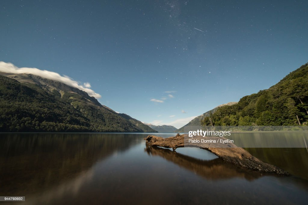 Scenic View Of Lake And Mountains Against Sky At Night : Stock Photo