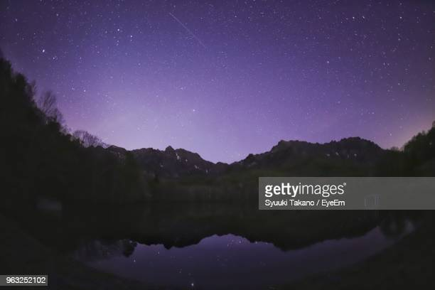 scenic view of lake and mountains against sky at night - 長野市 ストックフォトと画像