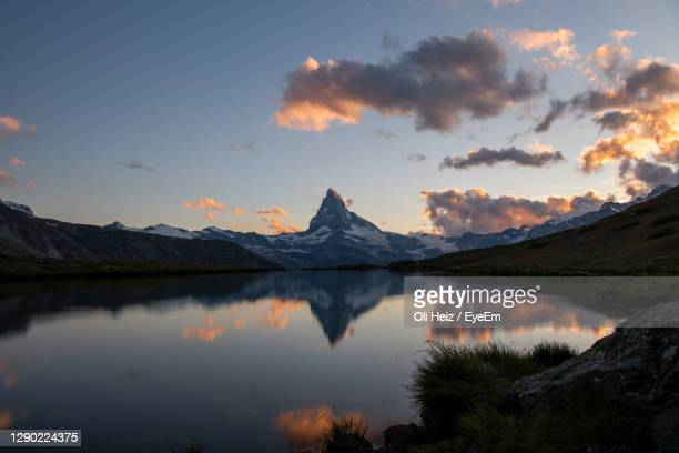scenic view of lake and mountains against sky during sunset - swiss alps stock pictures, royalty-free photos & images