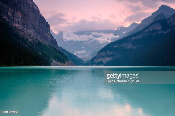 scenic view of lake and mountains against sky during sunset - lake louise lake stock photos and pictures