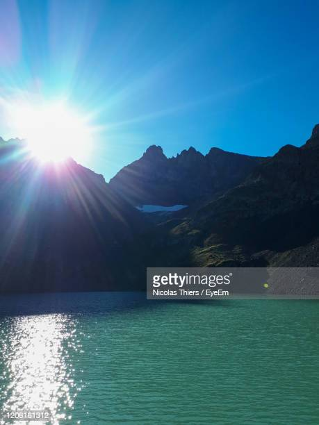 scenic view of lake and mountains against sky on sunny day - イゼール県 ストックフォトと画像