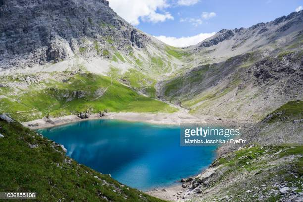 scenic view of lake and mountains against sky - vorarlberg stock-fotos und bilder