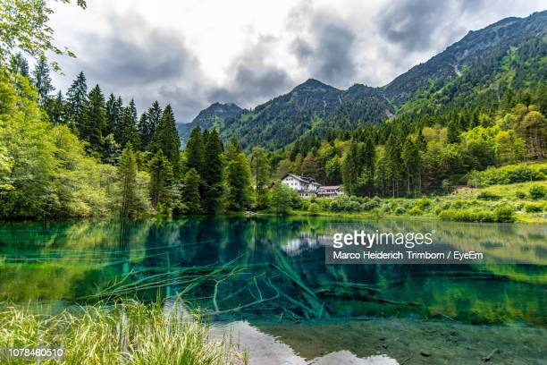 scenic view of lake and mountains against sky - oberstdorf stock pictures, royalty-free photos & images