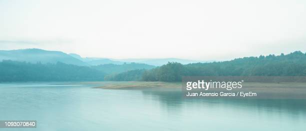 scenic view of lake and mountains against sky - asensio fotografías e imágenes de stock