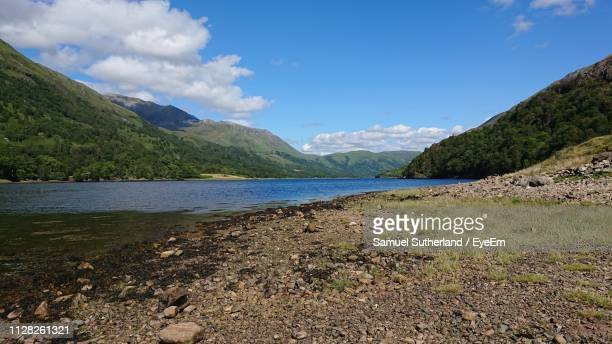 scenic view of lake and mountains against sky - pebble beach california stockfoto's en -beelden