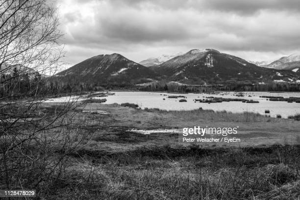 scenic view of lake and mountains against sky - weilacher stock-fotos und bilder