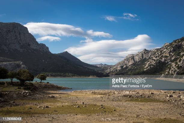 scenic view of lake and mountains against sky - wildnis stock-fotos und bilder
