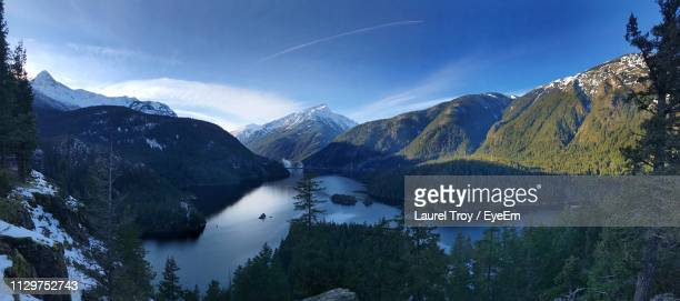 scenic view of lake and mountains against sky - diablo lake stock photos and pictures