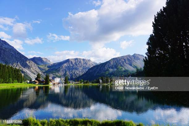 scenic view of lake and mountains against sky - アロサ ストックフォトと画像