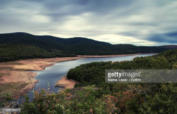 scenic view of lake and mountains against sky - burgos stock-fotos und bilder