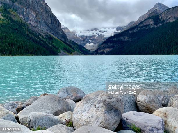 scenic view of lake and mountains against sky - futa stock photos and pictures
