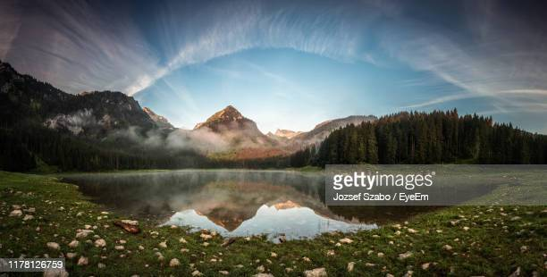 scenic view of lake and mountains against sky - lago reflection foto e immagini stock