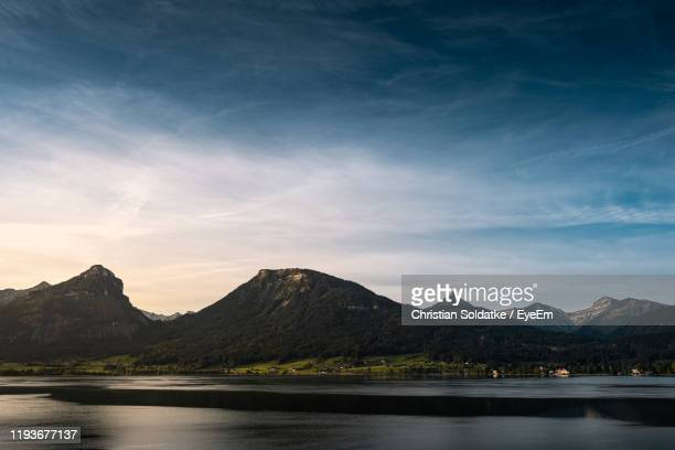 scenic view of lake and mountains against sky - christian soldatke stock pictures, royalty-free photos & images