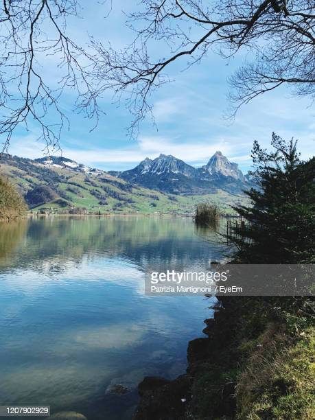 scenic view of lake and mountains against sky - schwyz stock pictures, royalty-free photos & images