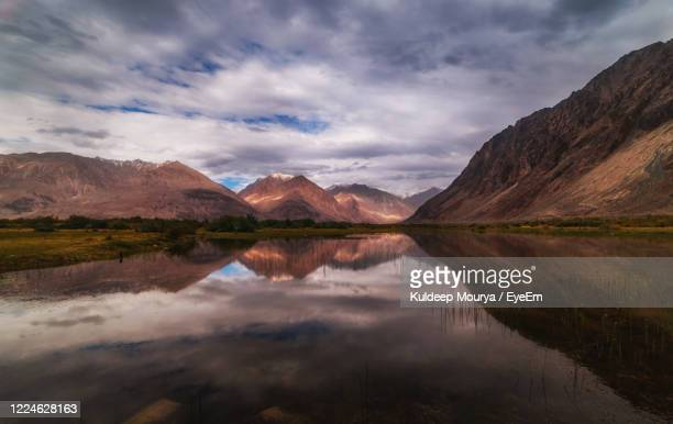 scenic view of lake and mountains against sky - rainy season stock pictures, royalty-free photos & images