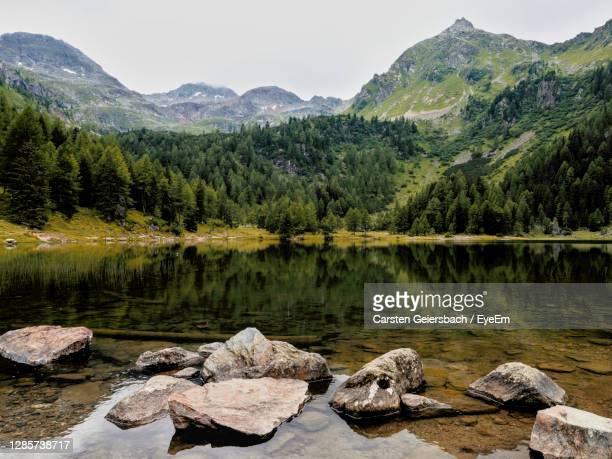 scenic view of lake and mountains against sky - schladming stock pictures, royalty-free photos & images