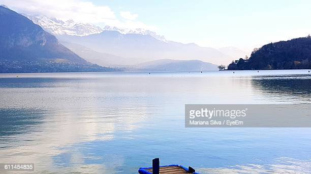 scenic view of lake and mountains against sky - フランス アヌシー ストックフォトと画像