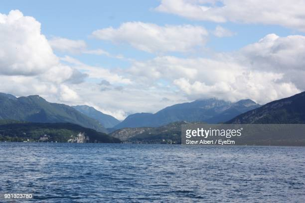 scenic view of lake and mountains against sky - land in sicht stock-fotos und bilder