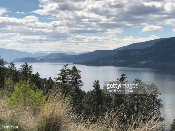 scenic view of lake and mountains against sky - kelowna stock pictures, royalty-free photos & images