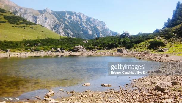 scenic view of lake and mountains against sky - küste stock-fotos und bilder
