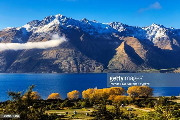scenic view of lake and mountains against sky - queenstown stock pictures, royalty-free photos & images