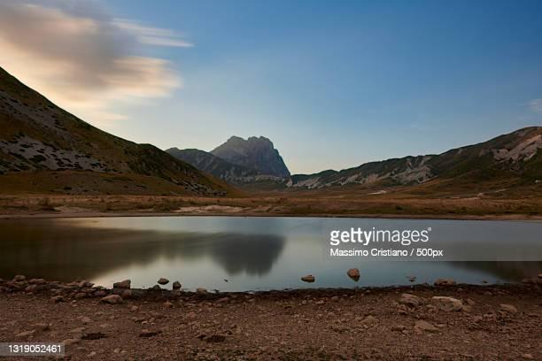 scenic view of lake and mountains against sky,campo imperatore,italy - parco nazionale del gran sasso e monti della laga foto e immagini stock