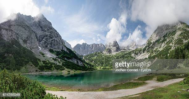 Scenic View Of Lake And Rocky Mountains Against Cloudy Sky