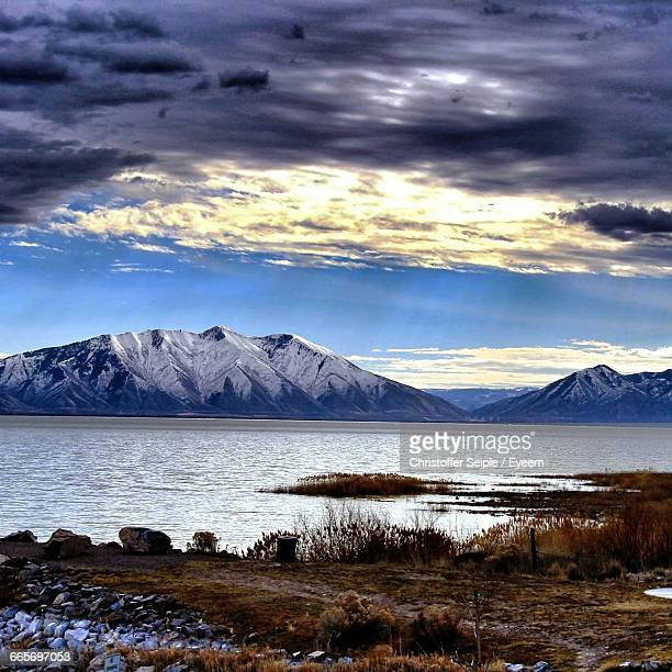 scenic view of lake and snow covered mountains against cloudy sky - provo foto e immagini stock