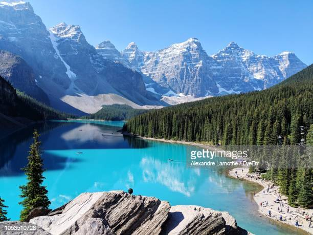 scenic view of lake and snowcapped mountains against blue sky - moraine lake stock pictures, royalty-free photos & images