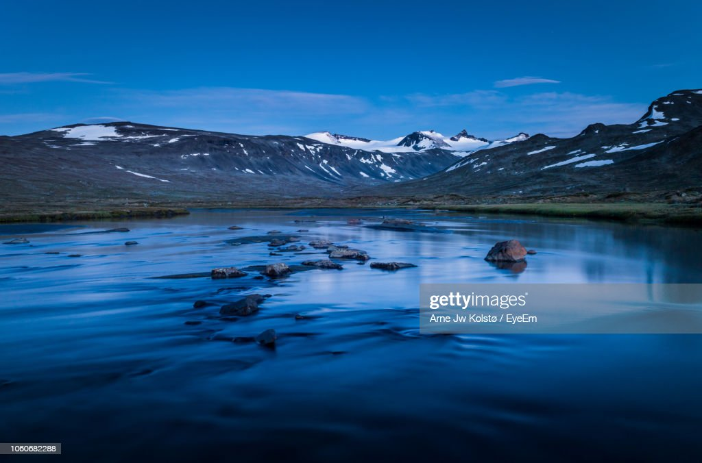 Scenic View Of Lake And Snowcapped Mountains Against Blue Sky : Foto de stock