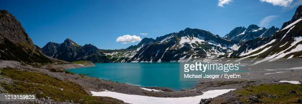 scenic view of lake and snowcapped mountains against blue sky - michael jaeger stock pictures, royalty-free photos & images